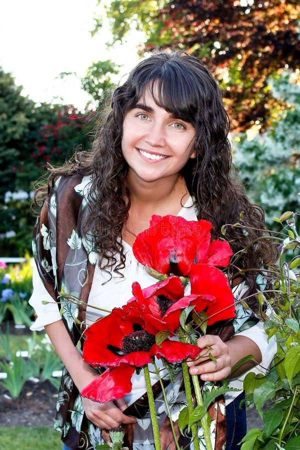Mujer y Poppy Flowers morenas felices fotos de archivo libres de regalías