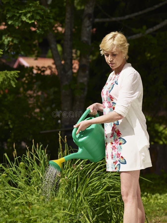 Mujer y pote del jardín imagen de archivo