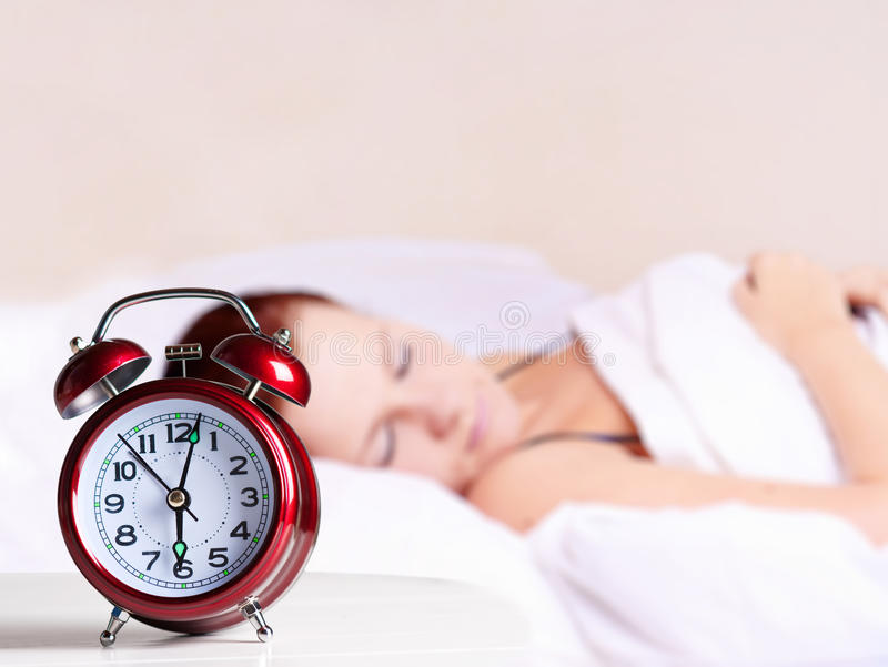 Mujer y reloj de alarma durmientes jovenes fotografía de archivo libre de regalías