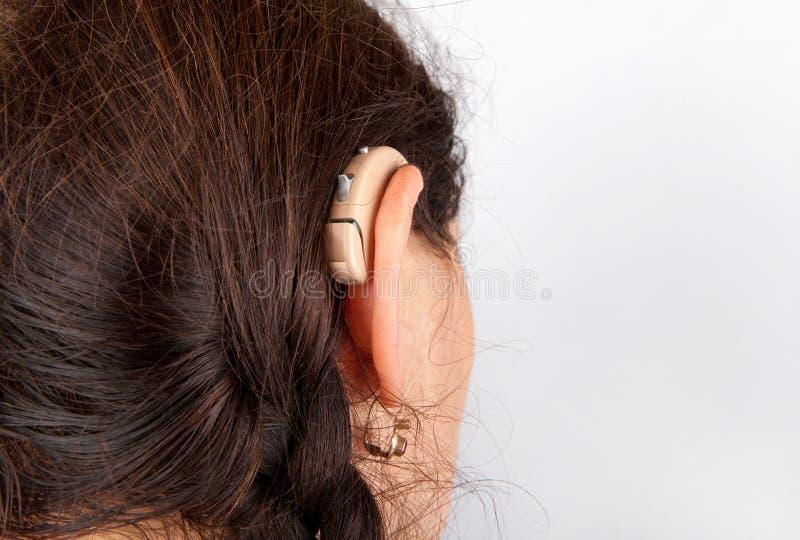 Mujer y su audífono fotografía de archivo libre de regalías