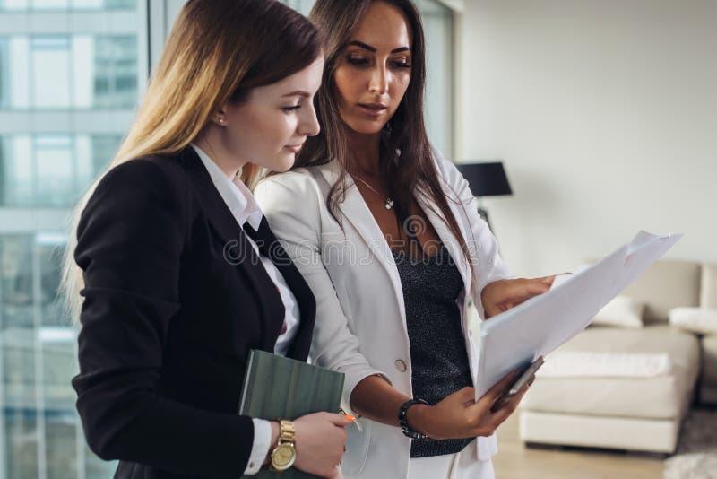 Mujer y su ayudante que llevan a cabo los documentos que discuten el plan empresarial y la estrategia en el lugar de trabajo imágenes de archivo libres de regalías