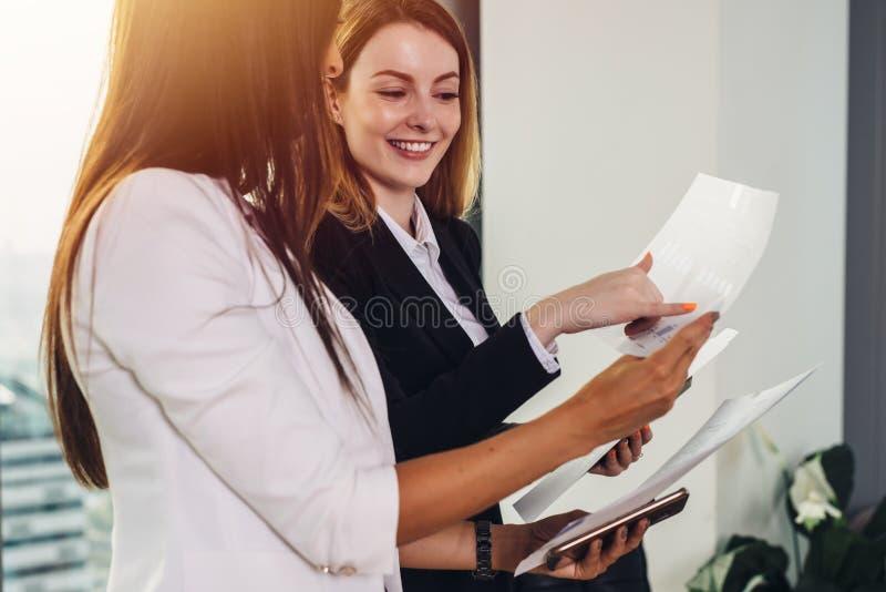 Mujer y su ayudante que llevan a cabo los documentos que discuten el plan empresarial y la estrategia en el lugar de trabajo imagenes de archivo