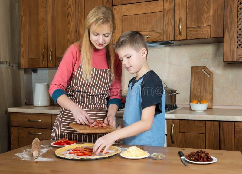 Mujer y su hijo que hacen la pizza en casa Muchacho del adolescente que cocina con su madre fotografía de archivo