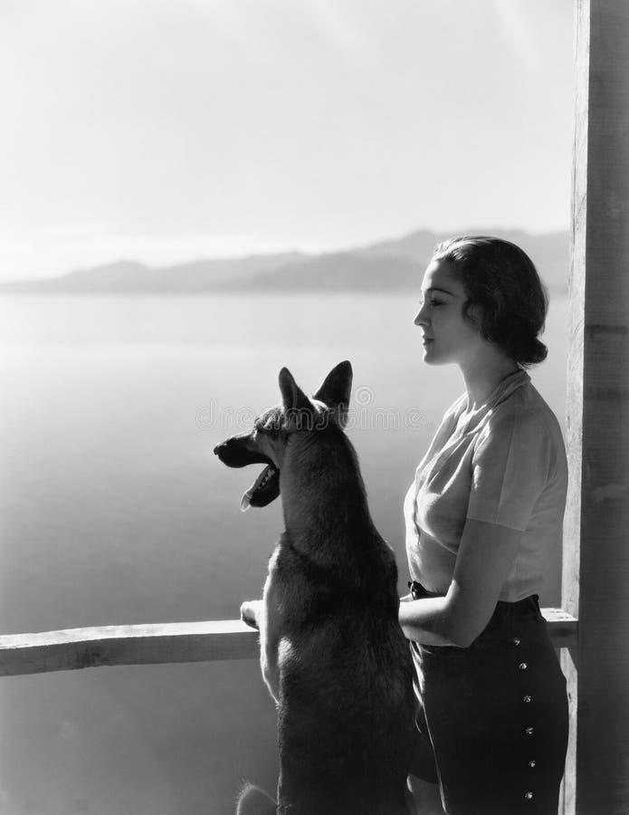 Mujer y su pastor alemán que pasan por alto un lago (todas las personas representadas no son vivas más largo y ningún estado exis fotografía de archivo