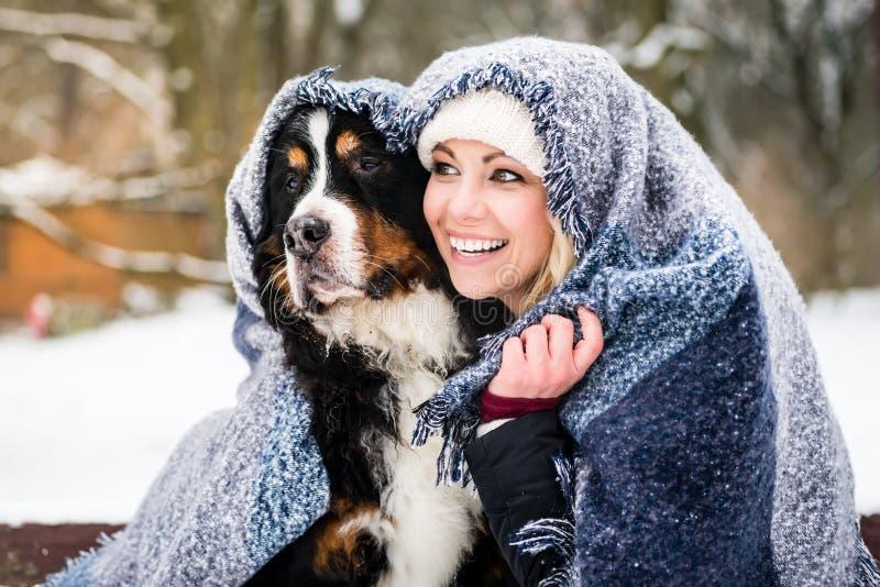 Mujer y su perro que consiguen calientes en día de invierno frío bajo blanke fotos de archivo libres de regalías