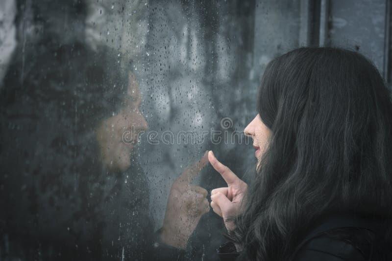 Mujer y su reflexión en ventana lluviosa imagenes de archivo