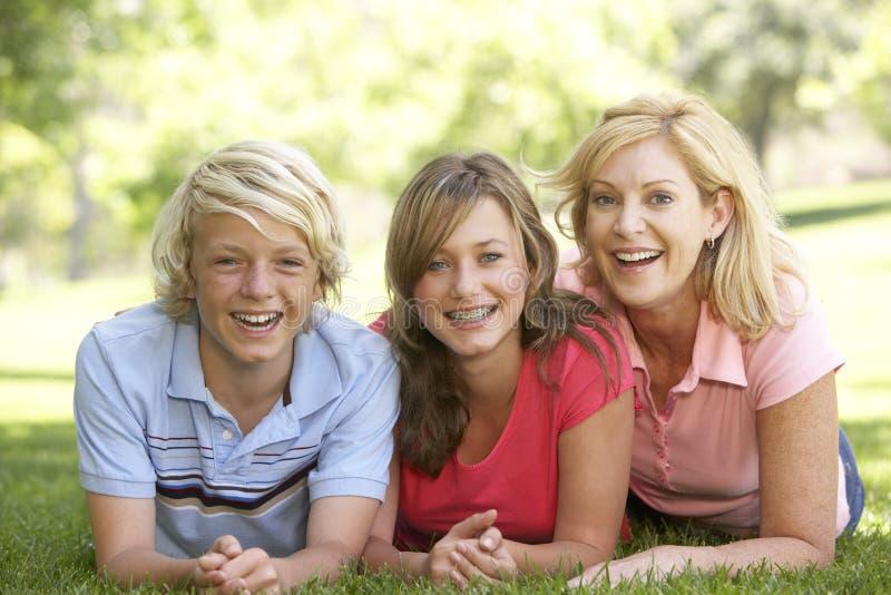 Mujer y sus niños adolescentes que mienten en hierba foto de archivo