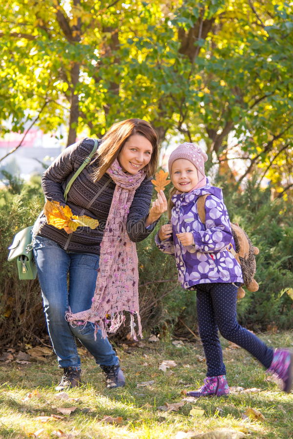 mujer y sus pequeñas hojas de otoño de las demostraciones de la hija imagen de archivo libre de regalías