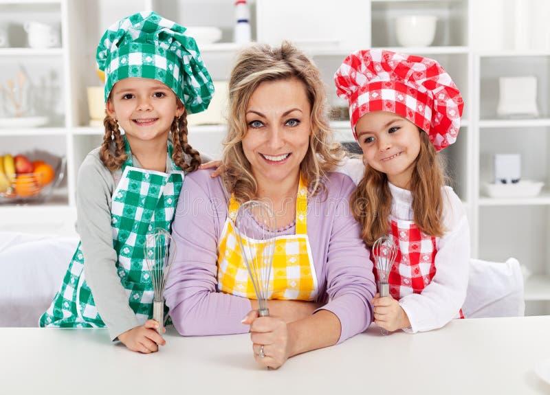 Mujer y sus pequeños cocineros del ayudante imagenes de archivo
