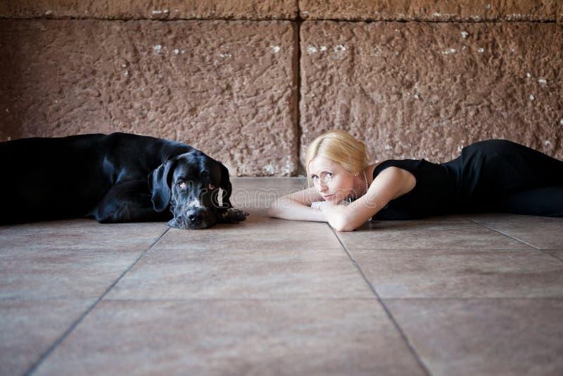 Mujer y un perro en el piso imagen de archivo