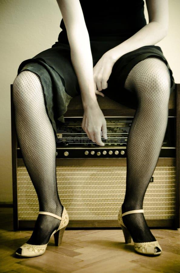 Mujer y una radio vieja foto de archivo