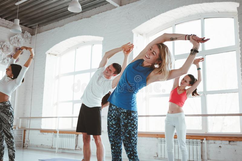 Mujeres adultas aptas y actitudes practicantes de la yoga del hombre en clase de la aptitud foto de archivo libre de regalías