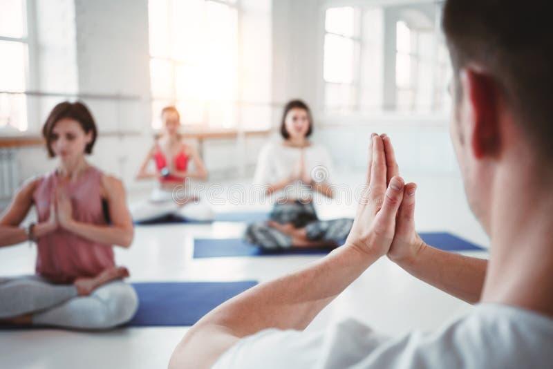 Mujeres adultas aptas y actitudes practicantes de la yoga del hombre en clase de la aptitud Grupo de gente fuerte sana que hace e foto de archivo