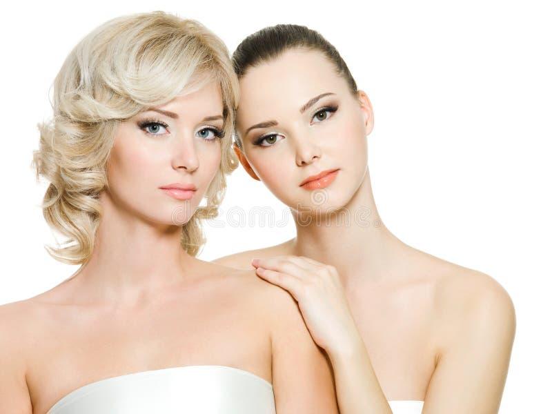 Mujeres adultas jovenes atractivas hermosas que presentan en blanco imagen de archivo