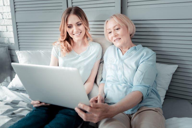Mujeres agradables alegres que se sientan delante del ordenador portátil foto de archivo libre de regalías