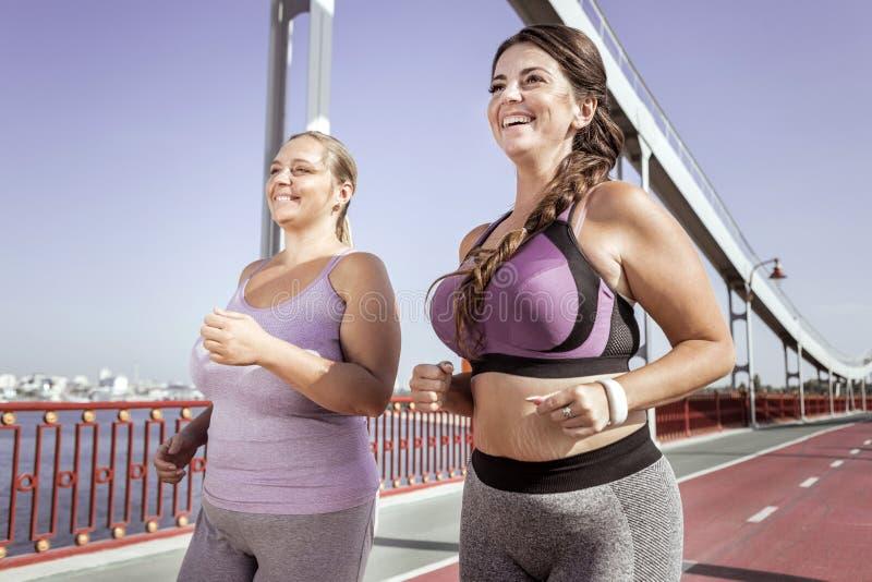 Mujeres alegres positivas que corren junto en el puente imagenes de archivo