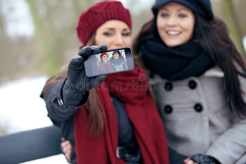 Mujeres alegres que gozan tomando imágenes al aire libre foto de archivo libre de regalías