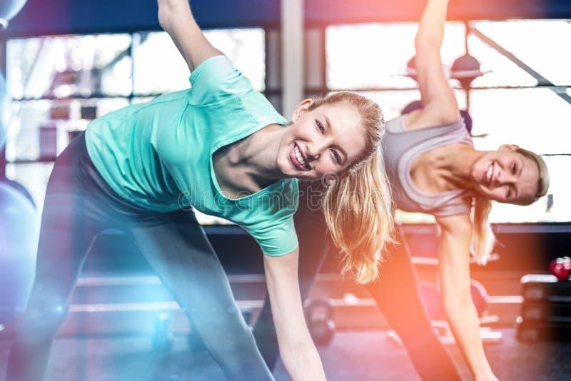 Mujeres aptas que estiran en gimnasio foto de archivo