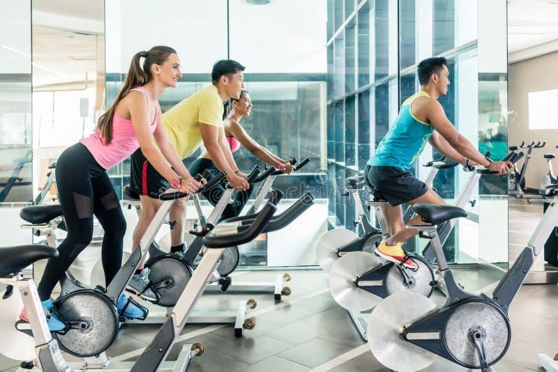 Mujeres aptas que queman calorías durante clase de ciclo interior en el club de fitness fotos de archivo libres de regalías