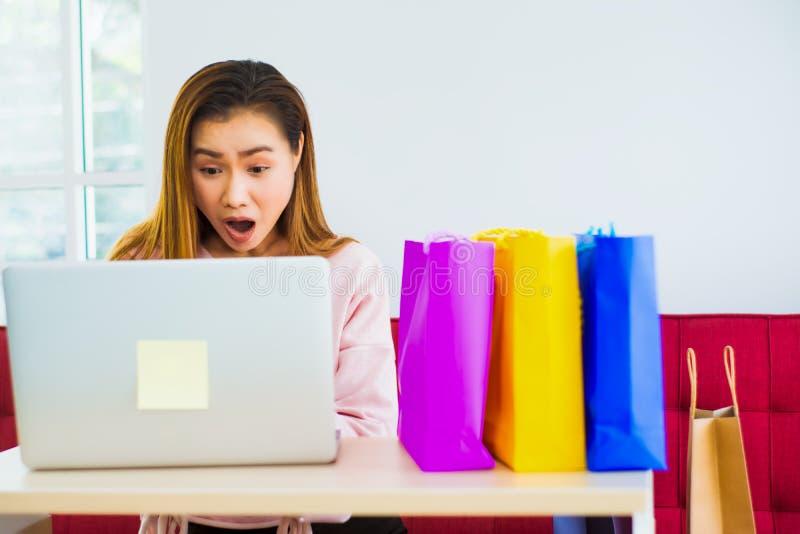 Mujeres asiáticas comprando en línea, gesto impactado con computadora y colorida bolsa de papel colocada en escritorios con el co fotografía de archivo