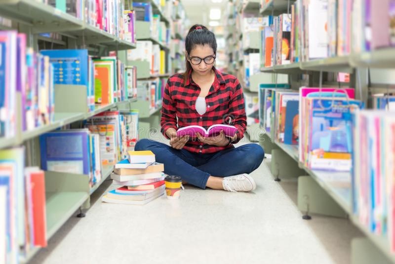 Mujeres asiáticas en la lectura de la biblioteca algo en un libro y elegir un libro en una biblioteca fotos de archivo libres de regalías
