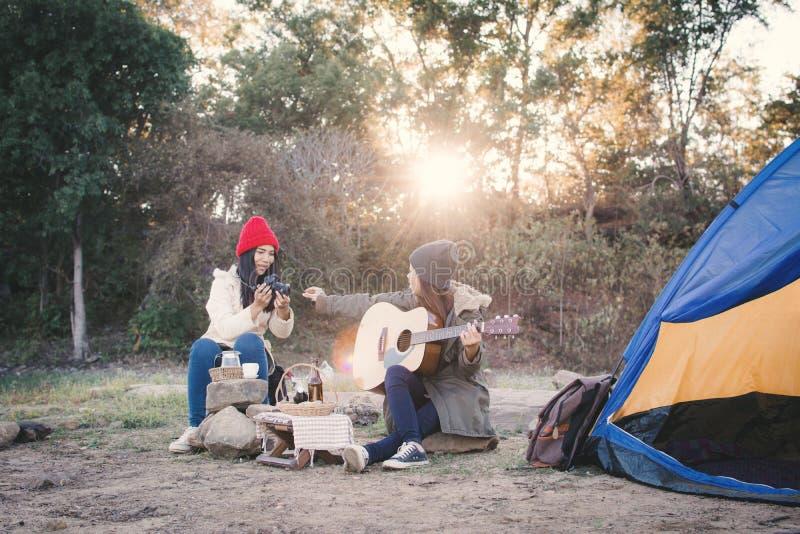 Mujeres asiáticas felices que tocan la guitarra en la estación del invierno de la naturaleza fotografía de archivo libre de regalías