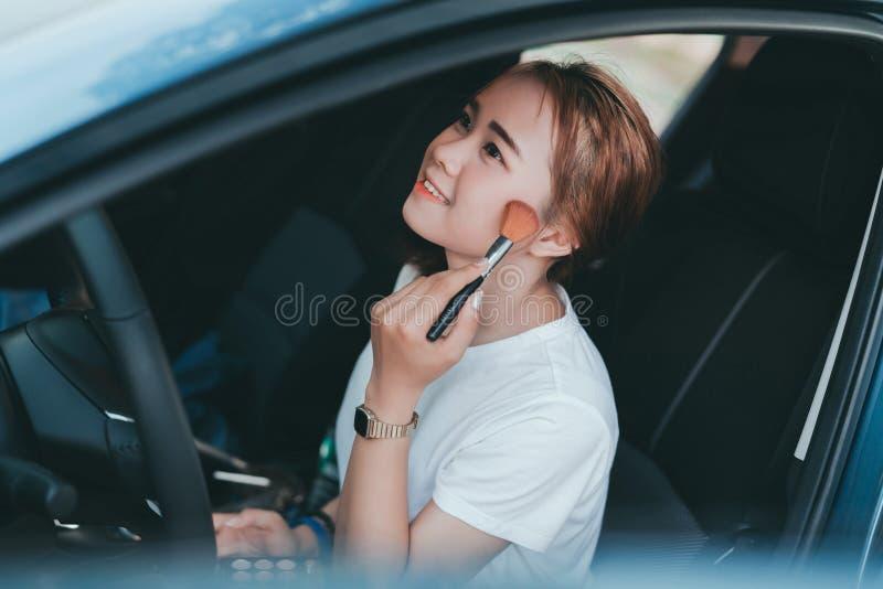 Mujeres asi?ticas hermosas que aplican maquillaje en coche interior imagen de archivo libre de regalías