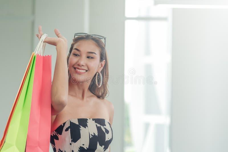 Mujeres asiáticas hermosas sosteniendo los bolsos que hacen compras que buscan la cosa que ella acaba de comprar Mujeres que sonr foto de archivo libre de regalías
