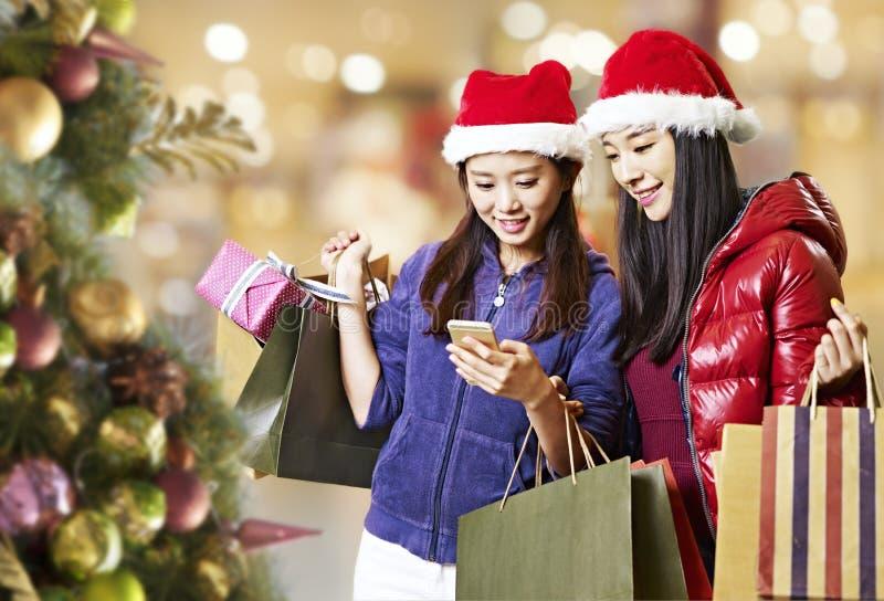 Mujeres asiáticas jovenes que usan el teléfono móvil durante compras de la Navidad imagen de archivo