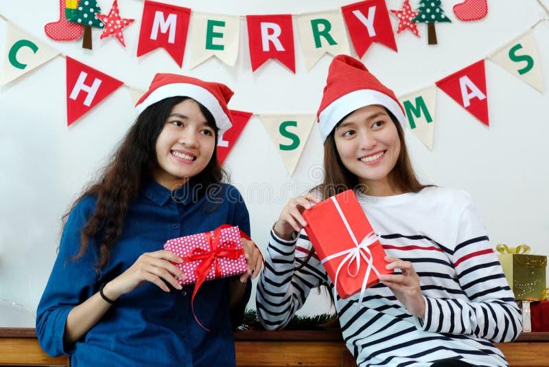 Mujeres asiáticas lindas jovenes que sonríen y que sostienen las cajas de regalo de la Navidad imagenes de archivo
