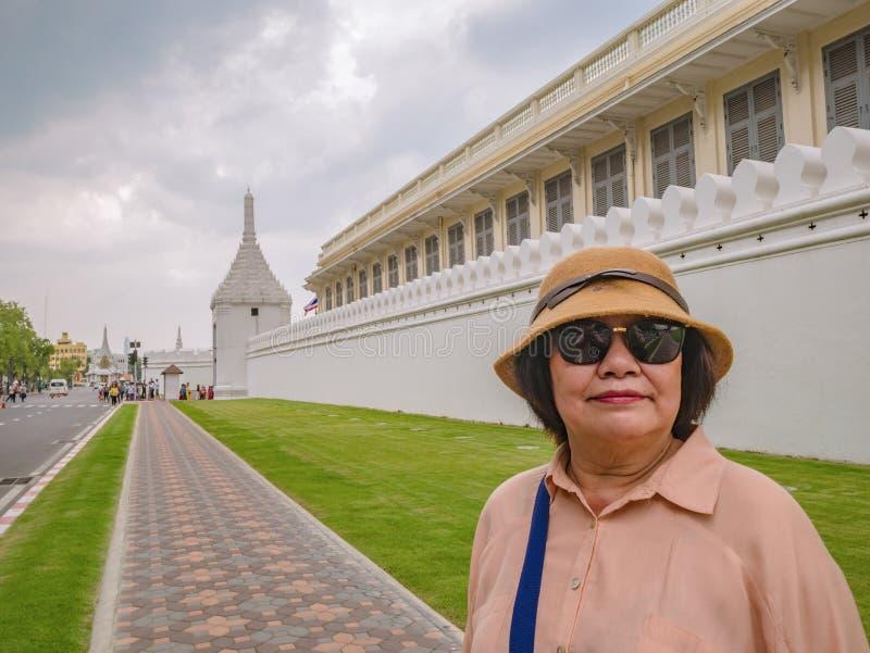 Mujeres asiáticas mayores del retrato con la pared de Wat Phrakeaw Temple en el templo principal de Bangkok fotografía de archivo libre de regalías