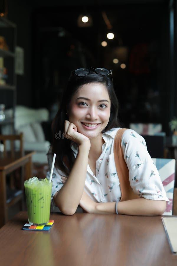 Mujeres asiáticas que sonríen y relajación feliz con té verde en una cafetería fotos de archivo libres de regalías