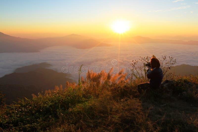 Mujeres asiáticas que toman la foto de la sol con mucha niebla por la mañana imagen de archivo