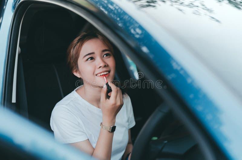 Mujeres asi?ticas hermosas que aplican maquillaje en coche interior foto de archivo