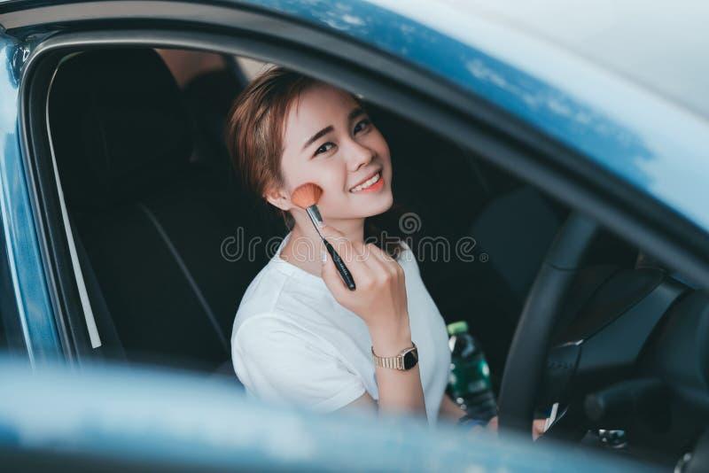 Mujeres asi?ticas hermosas que aplican maquillaje en coche interior fotografía de archivo libre de regalías