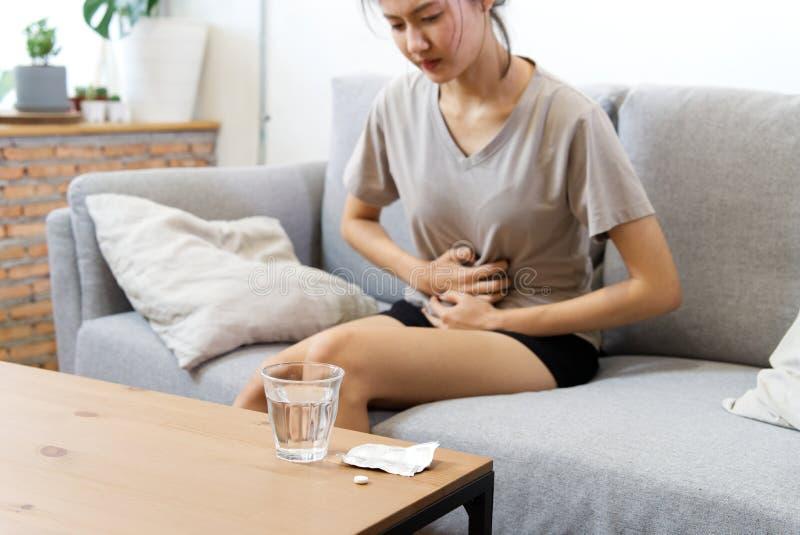 Mujeres asi?ticas jovenes en el sufrimiento del sof? del dolor de est?mago y tener cierta fiebre debido a la menstruaci?n imagenes de archivo