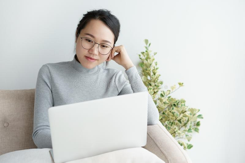 Mujeres asi?ticas que usan el ordenador port?til en casa, trabajo que se sienta y sonriente de la muchacha asi?tica en casa fotografía de archivo libre de regalías