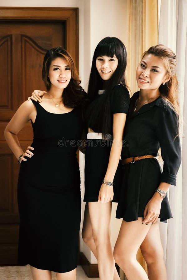 Mujeres atractivas asiáticas jovenes que se colocan en vestidos negros fotos de archivo libres de regalías