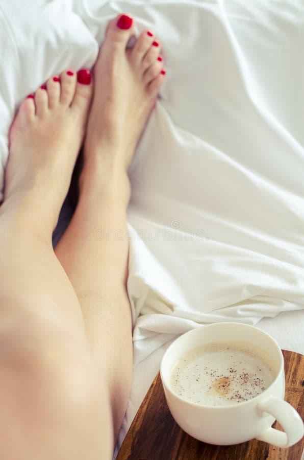 Mujeres atractivas que se relajan en malo con la taza de café caliente imagenes de archivo