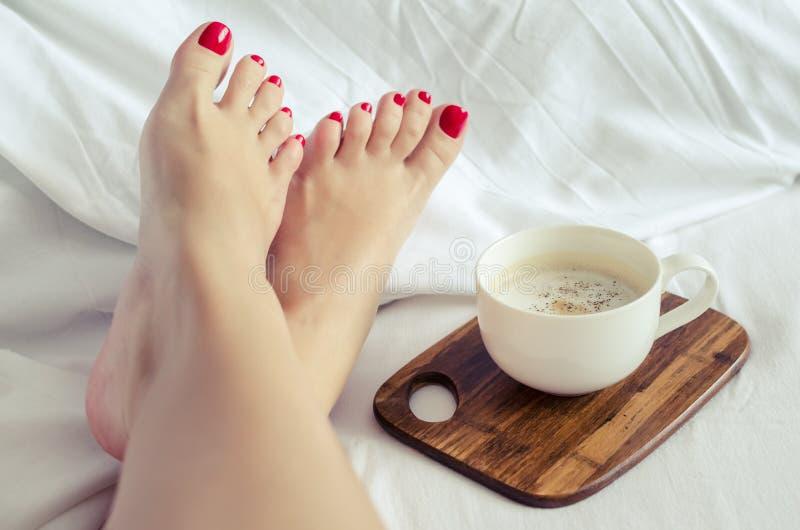 Mujeres atractivas que se relajan en malo con la taza de café caliente fotos de archivo libres de regalías