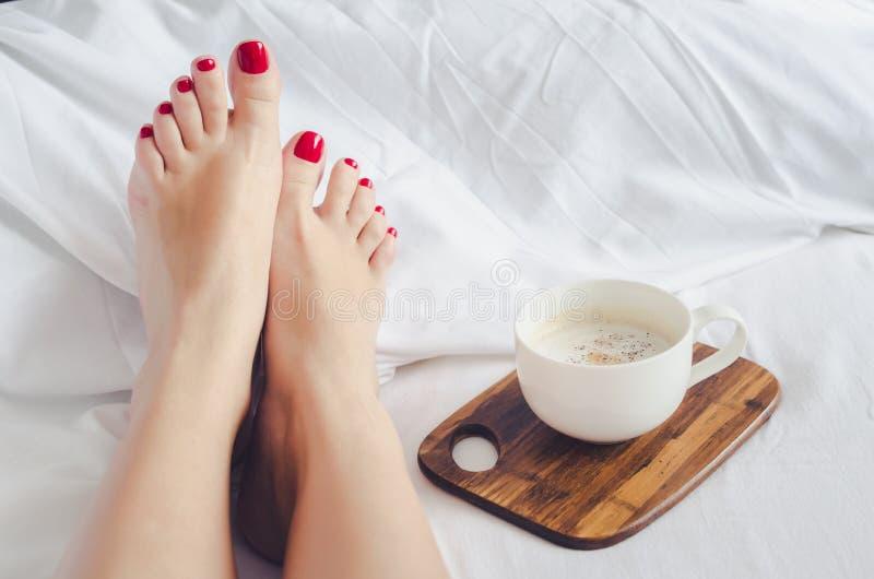 Mujeres atractivas que se relajan en malo con la taza de café caliente foto de archivo libre de regalías