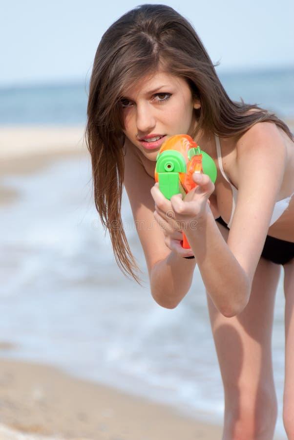 Mujeres bastante jovenes que juegan con el arma de agua en la playa imagen de archivo libre de regalías
