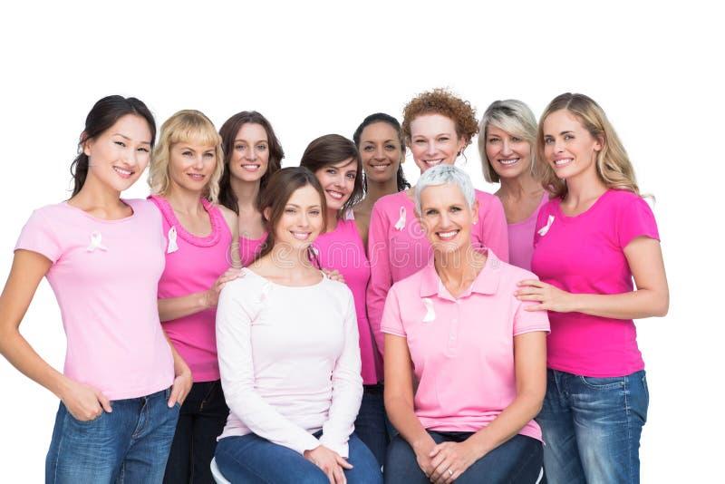 Mujeres bonitas alegres que plantean y que llevan el rosa para el cáncer de pecho fotos de archivo