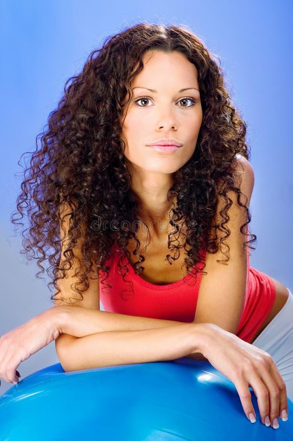 Mujeres bonitas del pelo de los rizos en bola azul de los pilates foto de archivo libre de regalías