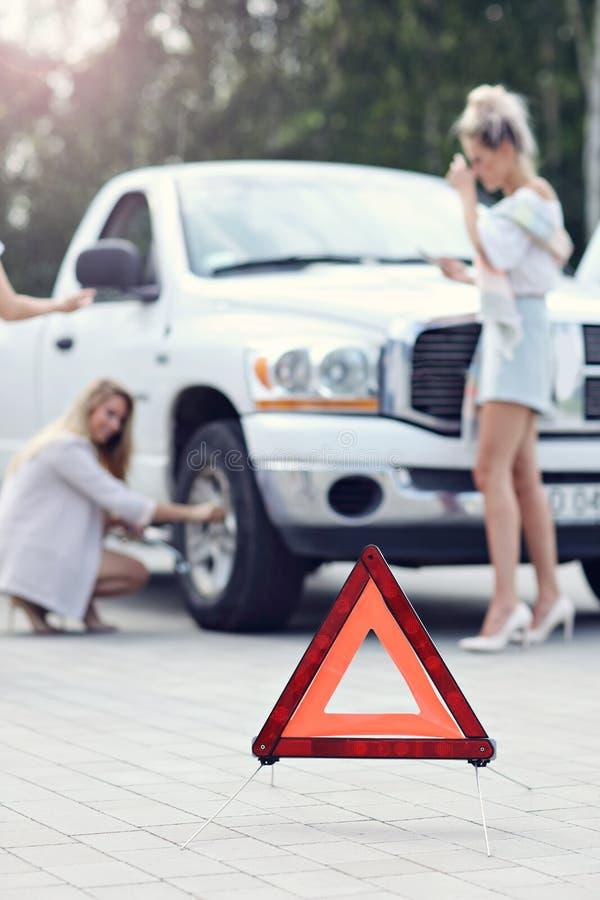 Mujeres bonitas que tienen problema con el coche en el camino imágenes de archivo libres de regalías