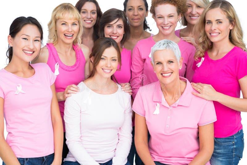 Mujeres bonitas voluntarias que plantean y que llevan el rosa para el cáncer de pecho imagen de archivo