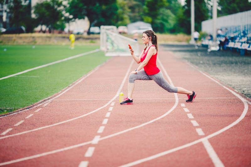 Mujeres caucásicas de la aptitud de los deportes que hacen calentamiento antes de ejercicio Atleta que estira las piernas que hac imagenes de archivo