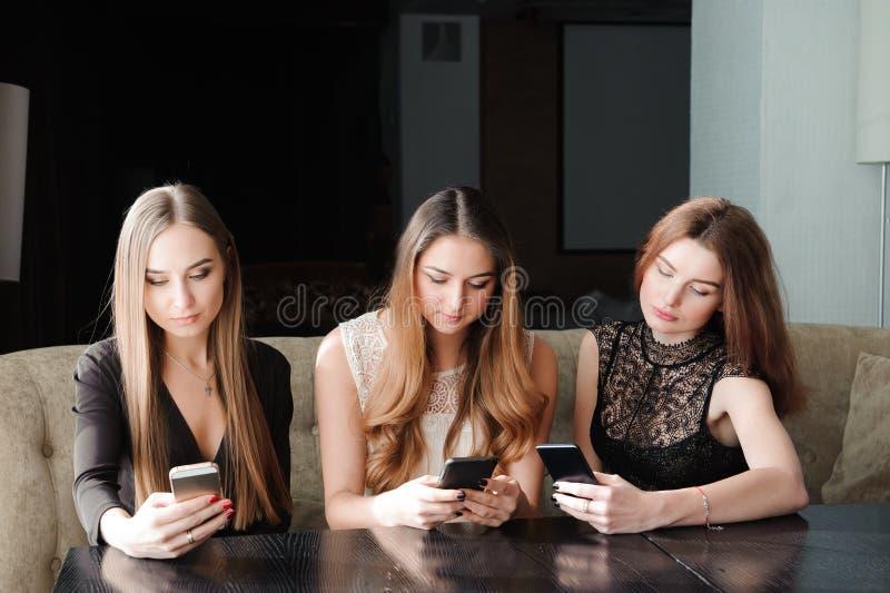 Mujeres caucásicas jovenes que usan el teléfono y diciendo no a la vida Concepto del apego de Smartphone imágenes de archivo libres de regalías