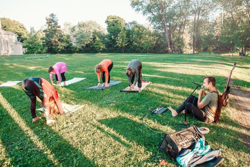 Mujeres caucásicas que hacen yoga en parque afuera en puesta del sol fotografía de archivo libre de regalías