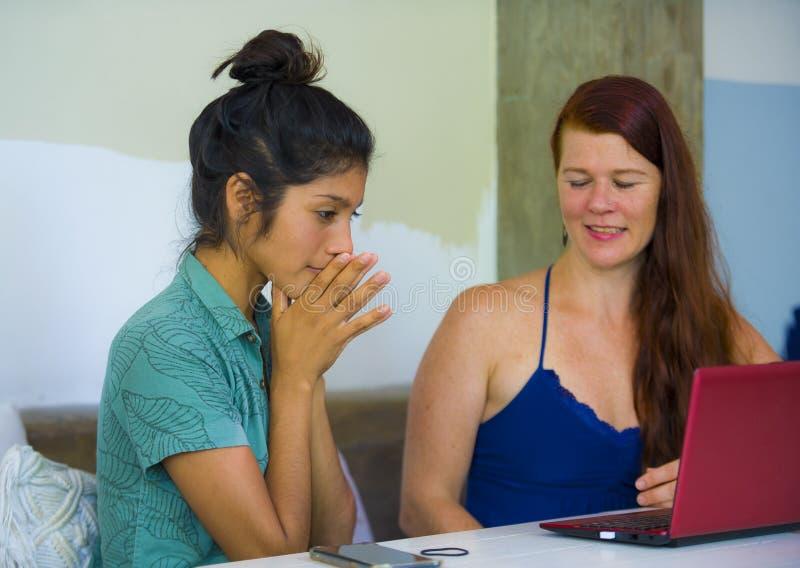 Mujeres caucásicas y latinas felices y hermosas jovenes que trabajan en el café de la oficina con el ordenador portátil que discu imagenes de archivo